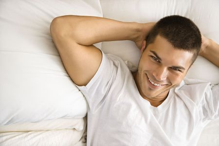 half length posed: High angle view of handsome Caucasian mid adult man lying with hands behind head  smiling.