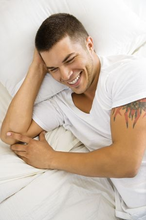 half length posed: High angle view of handsome Caucasian mid adult man lying in bed smiling.