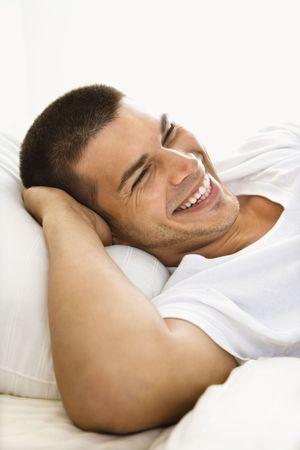 mid adult man: Hermoso mediados de adultos de raza cauc�sica hombre acostado con las manos detr�s de la cabeza sonriendo.