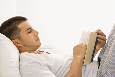 Side view of handsome Caucasian mid adult man lying in bed reading a book.