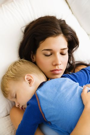 Caucasian mid adult woman with toddler son sleeping in bed.  photo
