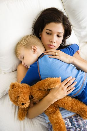 Caucasian mid adult woman holding sleeping toddler in bed.   photo