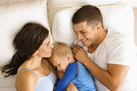 Caucasian mid adult parents with toddler son sleeping in bed. photo