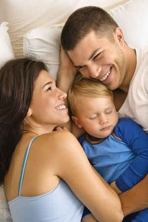 Caucasian mid adult parents cuddling with toddler son sleeping in bed. photo