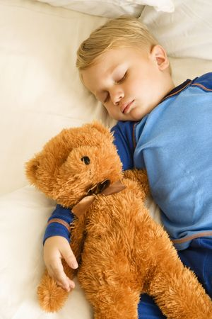 infants: Caucasian toddler boy sleeping in bed with teddy bear.
