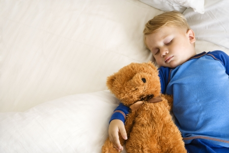 Caucasian toddler boy sleeping in bed with teddy bear. photo