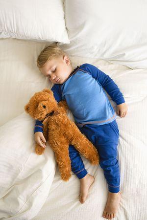 白人幼児の少年はテディー ・ ベアと一緒にベッドで寝ています。