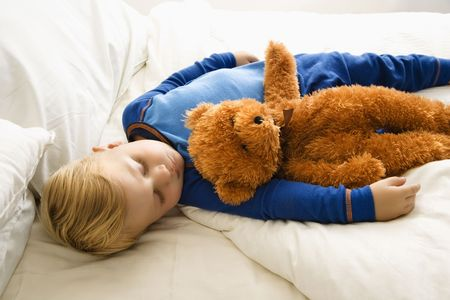 naptime: Caucasian toddler boy sleeping in bed with teddy bear.