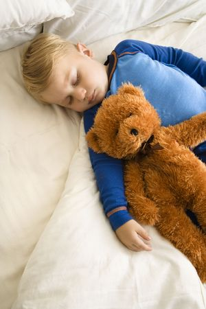 Caucasian toddler boy sleeping in bed with teddy bear.