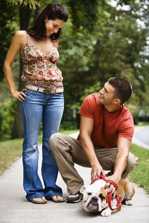 Caucasian mid adult couple with English Bulldog on sidewalk. Stock Photo