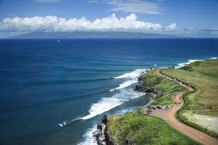 surfers: Aerial view of coastline with surfers and parked cars on Maui, Hawaii.