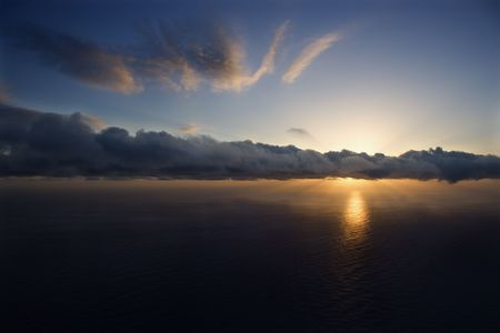 Aerial of sun setting over Pacific ocean with clouds. photo