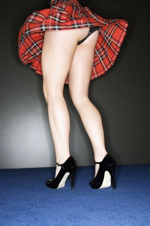 Upskirt view of Caucasian woman wearing plaid skirt with thong underwear. Stock Photo - 2029864