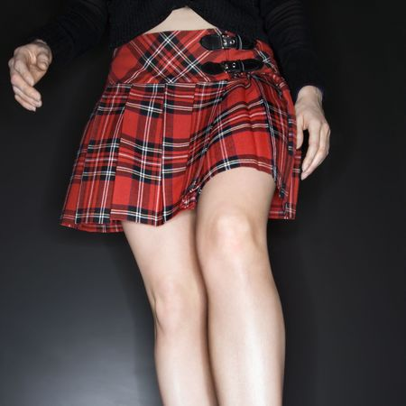 uniform skirt: Caucasian young woman wearing short plaid skirt.