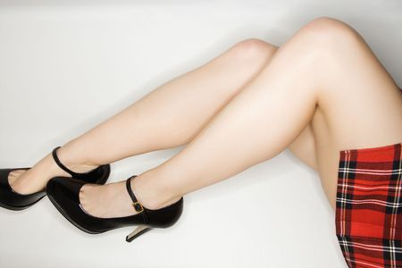 uniform skirt: Legs of Caucasian young woman in plaid skirt and high heels. Stock Photo
