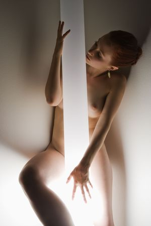 partially nude: Nude Caucasian woman standing with body wrapped around light pole.