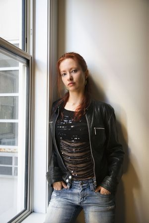 redhair: Pretty redhead young woman standing indoors by window leaning against wall with hands in jean pockets. Stock Photo