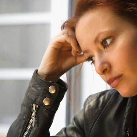 holding the head: Pretty redhead young woman indoors holding head on hand looking out window.