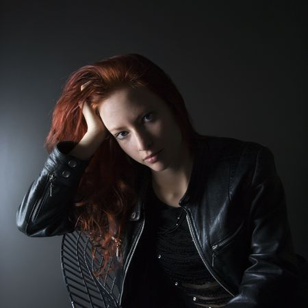 Portrait of pretty redhead young woman sitting in chair resting head on hand. Stock Photo