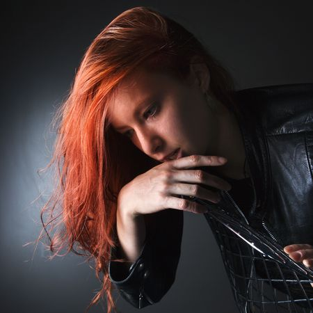 Pretty redhead young woman wearing leather jacket hanging over back of chair. photo