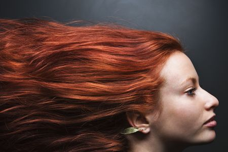 blown: Pretty redhead young woman profile with hair streaming out behind her.