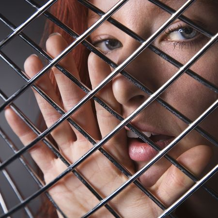 Pretty redhead young woman face and hand behind metal pattern. Stock Photo - 2044383