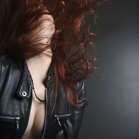 unrestrained: Pretty redhead young woman flipping head back with long hair flying out.