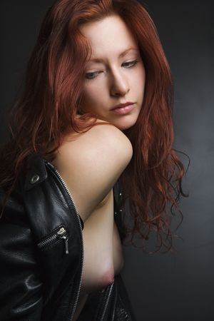 bare breasts: Pretty redhead young woman portrait with leather jacket pulled over shoulder exposing bare breasts. Stock Photo
