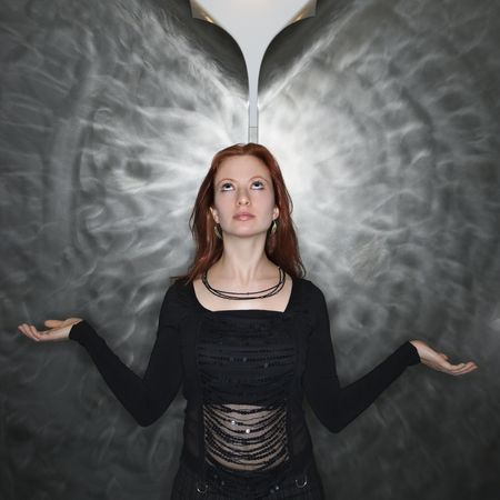 half length posed: Portrait of pretty young redhead woman in meditation pose looking up at parted metal background. Stock Photo