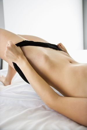 Close up of bare young woman sliding off black lace panties.