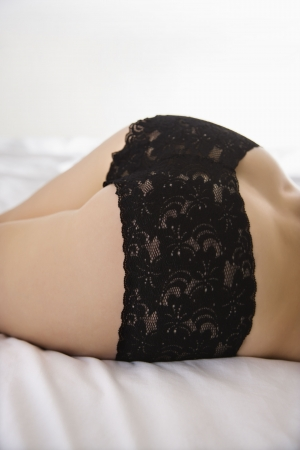 Back view of young woman wearing black lace panties.