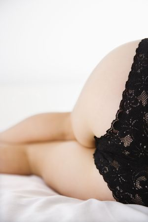 Close up rear view of young woman wearing black lace panties. photo