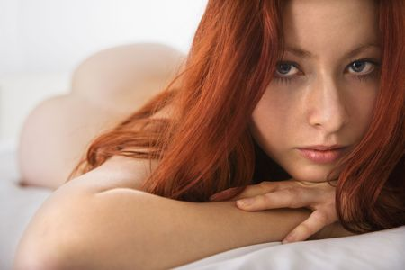Partially  pretty young redhead woman lying on bed making eye contact. Stock Photo