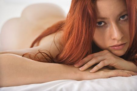 partially nude: Partially nude pretty young redhead woman lying on bed making eye contact.