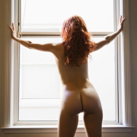 Back view of sexy nude redhead young woman standing in front of sunlit window. Stock Photo