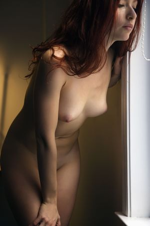 bare breasts: Pretty nude redhead young woman leaning to look out window. Stock Photo