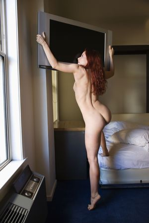 nude in bed: Rear view of pretty nude redhead young woman climbing on bed holding flat screen television.