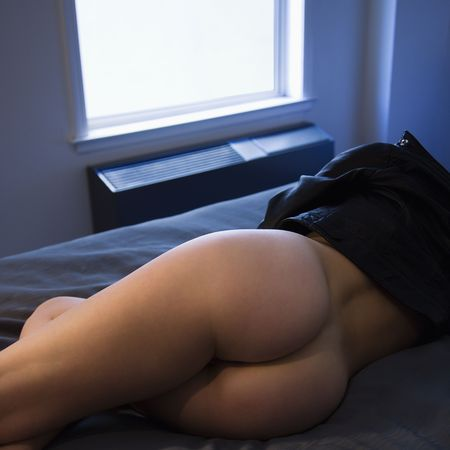 female butt: Partially  young woman lying in hotel room bed in leather jacket.