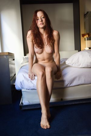 Front view of sexy pretty nude young redhead woman sitting on bed. Stock Photo - 2044310