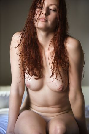 Front view of sexy pretty nude young redhead woman sitting on bed. photo