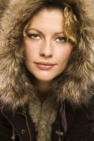 Caucasian young adult woman wearing coat with fur hood looking at viewer. photo