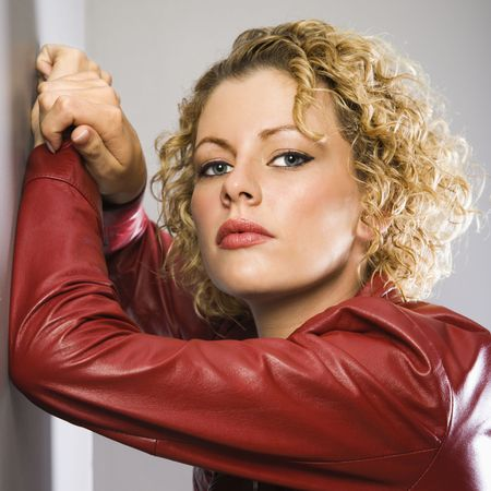 Caucasian young adult woman in red jacket with arms raised leaning on wall looking at viewer. Stock Photo - 2044405