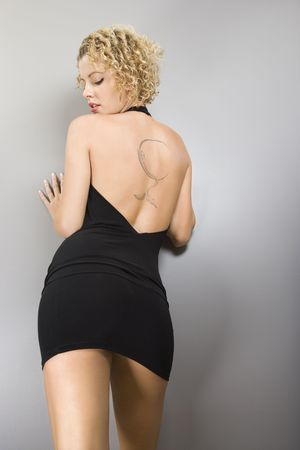 Back view of Caucasian young adult woman leaning on wall with tattoo. Stock Photo - 2044295