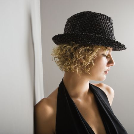 fedora hat: Profile of Caucasian young adult woman wearing fedora hat with eyes closed.