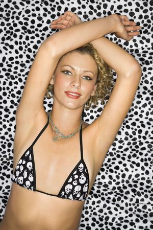 Caucasian young adult woman in bra on leopard print background looking at viewer with arms above head.  photo