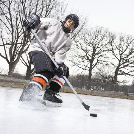 hockey player: Boy in ice hockey uniform skating on ice rink moving puck.