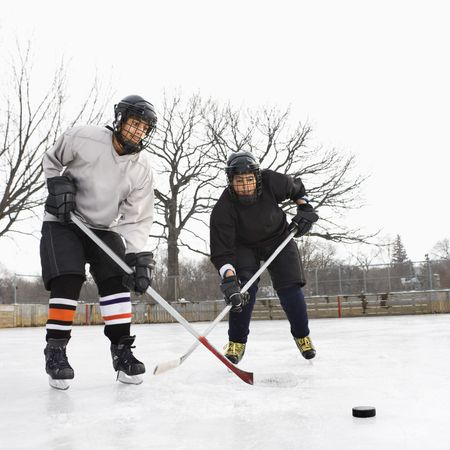 pre teen boys: Two boys in ice hockey uniforms playing hockey on ice rink. Stock Photo