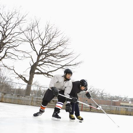 shove: Two boys in ice hockey uniforms playing hockey on ice rink. Stock Photo