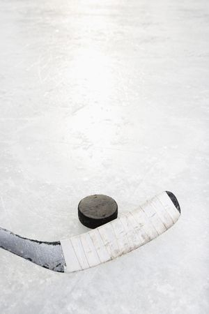 ice hockey puck: Close up of ice hockey stick on ice rink in position to hit hockey puck.