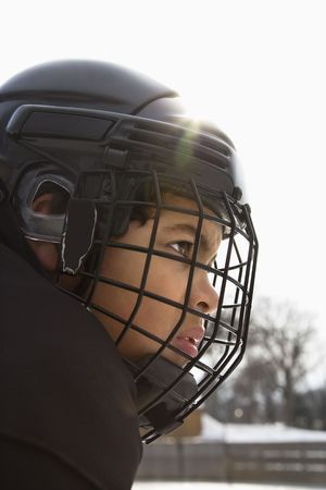 Close up of ice hockey player boy in cage helmet with look of concentration.